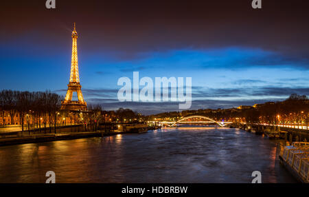 The Eiffel Tower illuminated at twilight with the Seine River banks and the Debilly Footbridge. Paris, France - Stock Photo