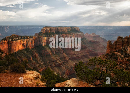 Shafts of evening light pierce the building thunderstorms over Wotons Throne on the North Rim of Arizona's Grand Canyon National Park.