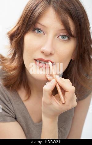 Portrait of a woman applying lipliner - Stock Photo
