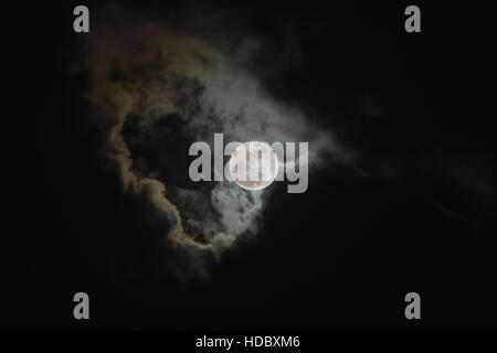 Bright full moon on cloudy scene of night sky. Elements of this image furnished by NASA. - Stock Photo