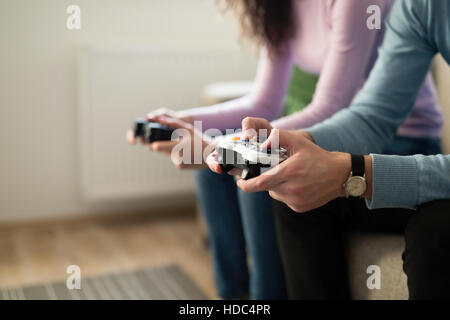 Young people playing video games on console controllers - Stock Photo