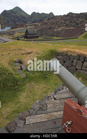 Old gun, Norwegian Stave Kirke and edge of the lava field caused by the eruption of Eldfell in 1973, Heimaey, southern - Stock Photo