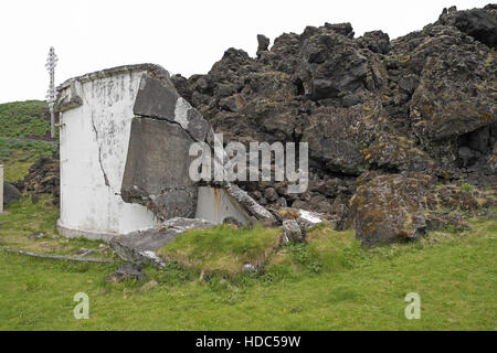 Edge of the lava field and destroyed concrete tank caused by the eruption of Eldfell in 1973, Heimaey, Iceland. - Stock Photo