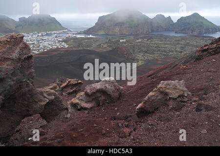Part of Heimaey (left) seen over volcanic rocks and lava field from summit of Eldfell, Heimaey, Vestmannaeyjar Islands, - Stock Photo