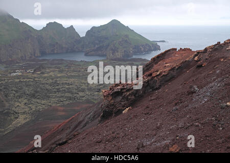 Part of Heimaey (left) seen over volcanic rocks and lava field from flanks of Eldfell, Heimaey, Vestmannaeyjar Islands, - Stock Photo