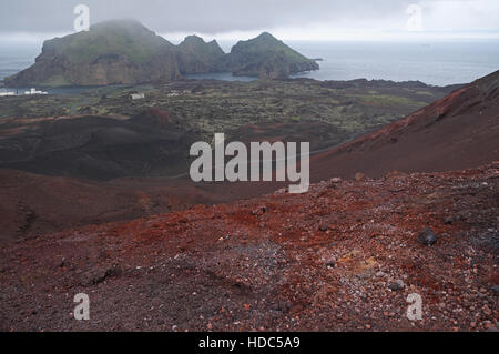 Town of Heimaey seen over volcanic rocks and lava field from Eldfell, Heimaey, Vestmannaeyjar Islands, southern - Stock Photo