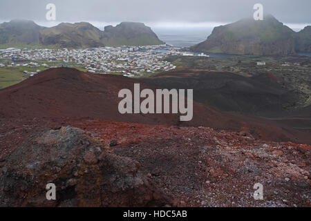Village of Heimaey seen over volcanic rocks and lava field from Eldfell, Heimaey, Vestmannaeyjar Islands, southern - Stock Photo