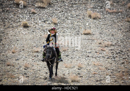Bayan Ulgii, Mongolia, October 4th, 2015: Eagle huntress  riding a horse - Stock Photo