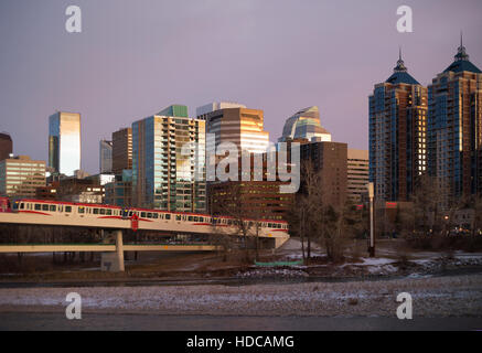 Light rail electric train powered by wind energy crossing Bow River into downtown Calgary, pedestrian bridge underneath - Stock Photo