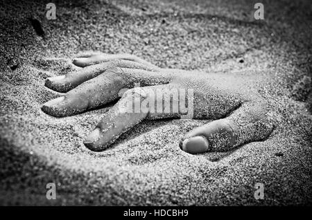 on the beach hand in rigor mortis protruding from the sand - Stock Photo