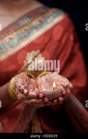 Young Indian girl in a traditional indian sari holding a lit oil lamp - Stock Photo