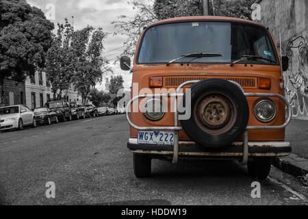 Old Volkswagen van ready for tripping, the contrast between the city in black and white and the orange of the van - Stock Photo