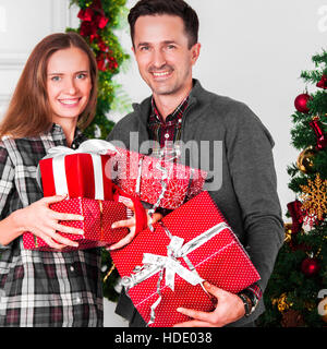 Happy couple with christmas gifts near decorated tree - Stock Photo