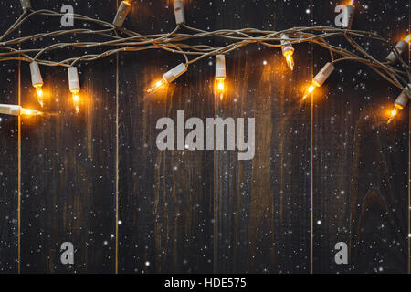 Christmas Background Lights And Snow With Copy Space On Old Wooden Board