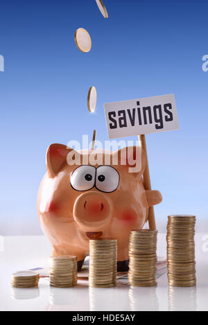 Concept savings with coins falling on piggy bank with savings billboard and stacked coins on reflective white glass - Stock Photo