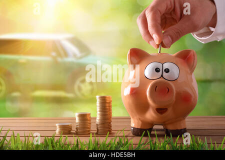 Concept savings with hand putting money into a piggy bank saving to buy a car. Objects on wooden table and nature - Stock Photo