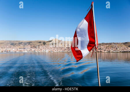 Peruvian flag on tourist boat on Lake Titicaca, City of Puno in background, Puno, Peru - Stock Photo
