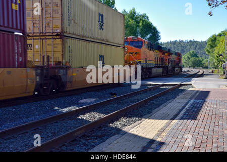 Two BNSF diesel locomotives at front of train pulling long line of wagons with shipping containers at Flagstaff, - Stock Photo