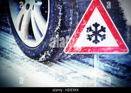 Car tires on winter road with traffic sign - Stock Photo