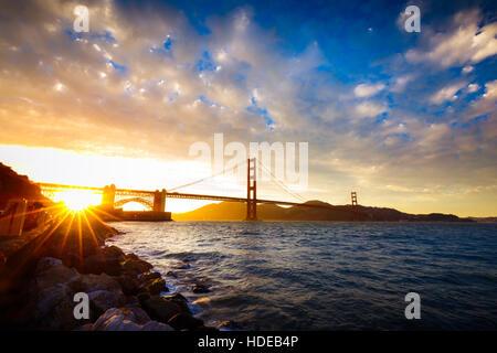 Sunset at the Golden Gate Bridge with sun starburst, San Francisco, California - Stock Photo