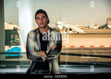 Portrait of a man in checkered shirt posing for camera at an airport - Stock Photo