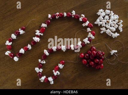 Popcorn on a needle and thread being added to partially made Christmas garland. More popcorn and cranberries on - Stock Photo