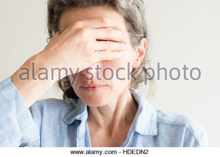 Close up of middle aged woman with hand covering eyes - Stock Photo