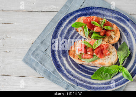 Bruschetta with tomatoes and basil on the ceramic plate horizontal - Stock Photo