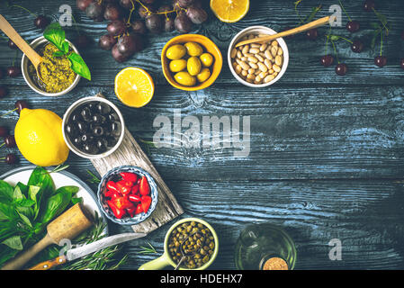 Concept of Mediterranean cuisine. Different fruit , herbs and appetizers on the wooden table - Stock Photo