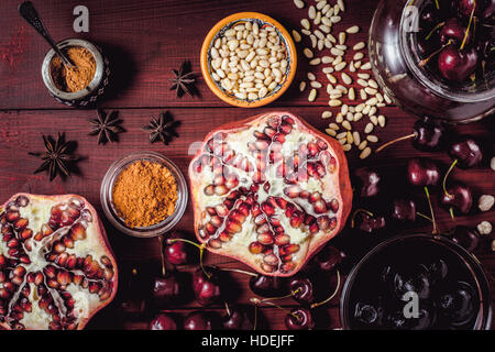Different fruit and spices on the red wooden table. Concept of oriental fruits top view - Stock Photo
