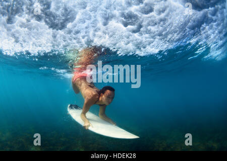 Girl in bikini in surfing action. Surfer with surf board dive underwater under breaking ocean wave Extreme water - Stock Photo