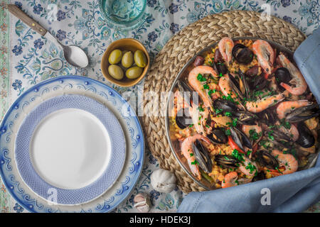 Paella on the metal plate on the beautiful napkin with tableware top view Stock Photo