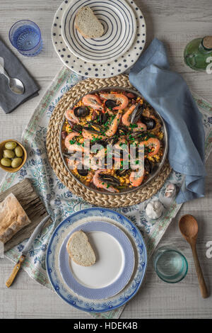 Paella on the metal plate on the beautiful napkin with tableware and bread vertical - Stock Photo