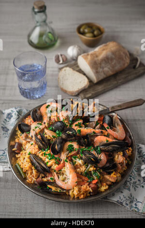 Paella in the metal plate on the wooden table - Stock Photo