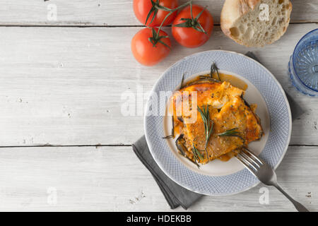 Eating moussaka in the white table with tomatoes and bread  top view - Stock Photo