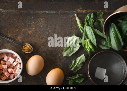 Ingredients for Florentine eggs with spinach on the rusty background top view - Stock Photo