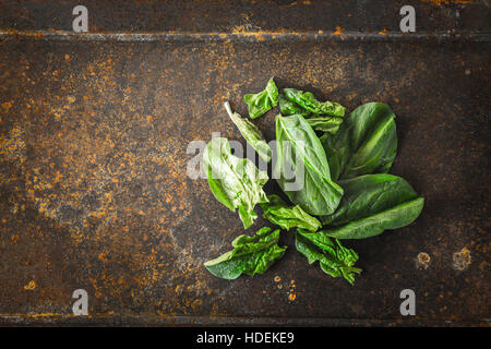 Fresh spinach on the metal rusty background top view - Stock Photo