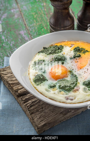 Florentine eggs with pureed spinach on the wooden table vertical - Stock Photo