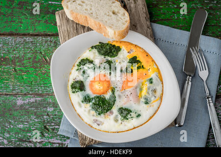 Florentine eggs with pureed spinach on the old wooden board - Stock Photo