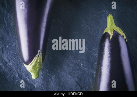 Eggplants on the dark stone background top view Stock Photo