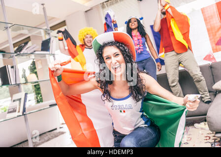 Italian fan supporting her team - Friendswatching a sport event on tv at home - Stock Photo