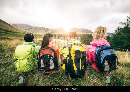 Four backpackers looking at sunset over the mountains - Hikers talking and relaxing after an excursion in the nature - Stock Photo