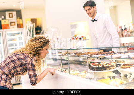 Woman buying some cookies and cakes in a pastry shop - Beautiful girl  in front of sweet candy food store window - Stock Photo