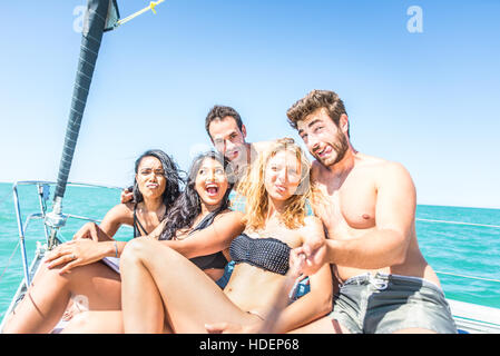 Group of friends taking selfie from the boat - Multi-ethnic young people having fun and partying on a sailing ship - Stock Photo