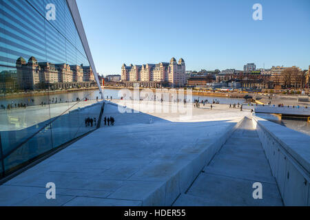 View on a side of the National Oslo Opera House with city reflected in glass - Stock Photo