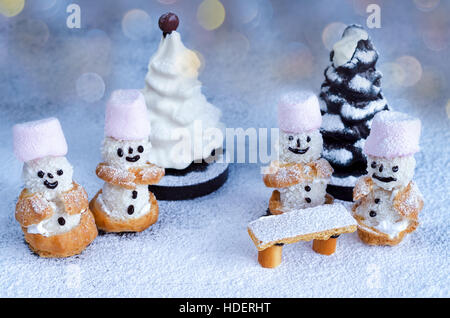 Little cakes snowmen and chocolate trees in powdered sugar - Stock Photo