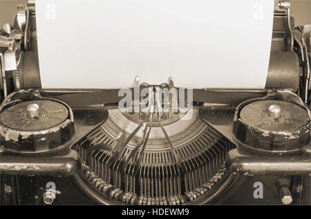 Old typewriter and blank sheet of paper for your text, sepia style - Stock Photo