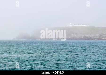 Sea mist rolling in over St Ann's Head on a summers morning. - Stock Photo