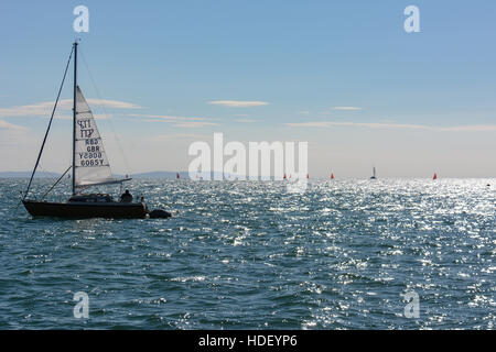 An anchored yacht with the mainsail partly raised as a steadying sail watches dinghy racing on a summers morning. - Stock Photo