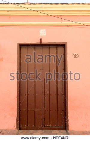 Colourful wooden door in old home. Spanish colonial architectural detail in urban houses of tropical Santiago de - Stock Photo